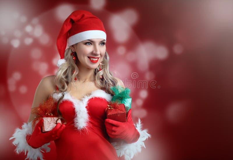 佩带圣诞老人的美丽的女孩给与圣诞节礼物我穿衣 免版税库存照片