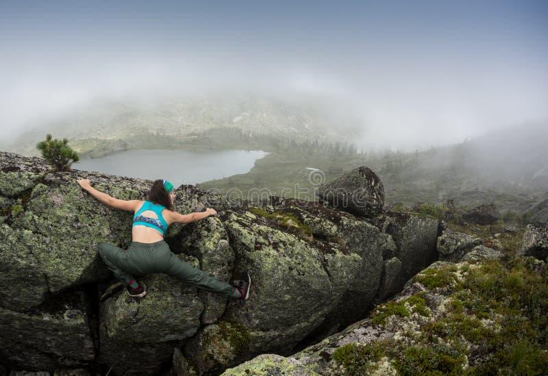 佩带在上升的设备的少妇站立在室外一个石的岩石前面和准备上升,背面图 免版税库存照片