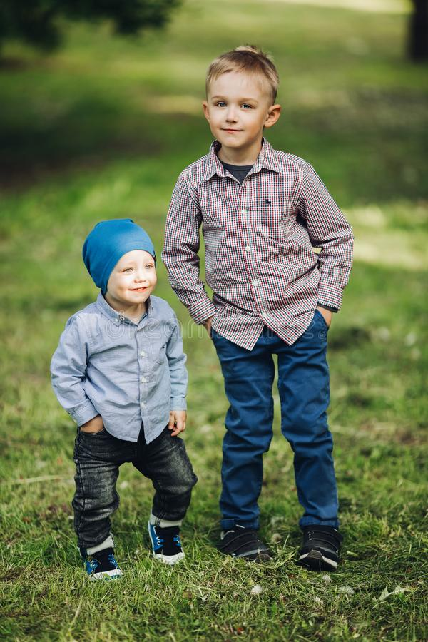 佩带在偶然看起来的两个小男孩摆在握在口袋的公园手 免版税图库摄影