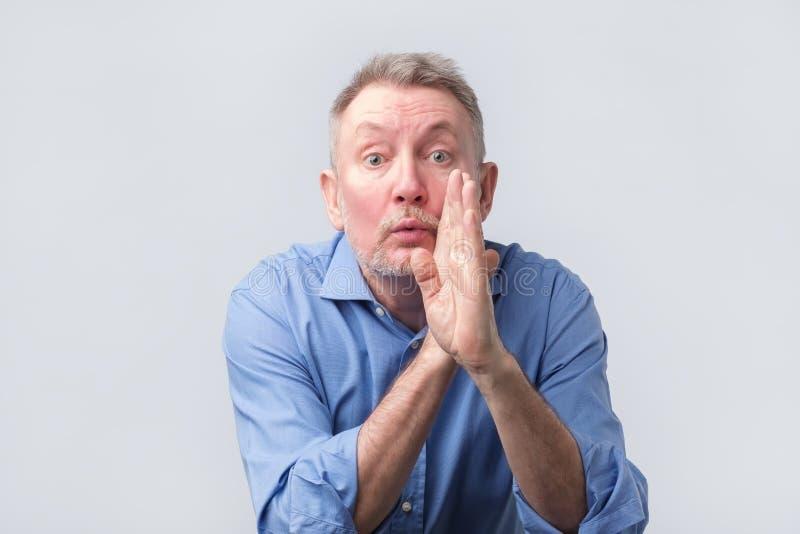 佩带在嘴的老人蓝色衬衣举行手告诉秘密谣言 免版税库存照片