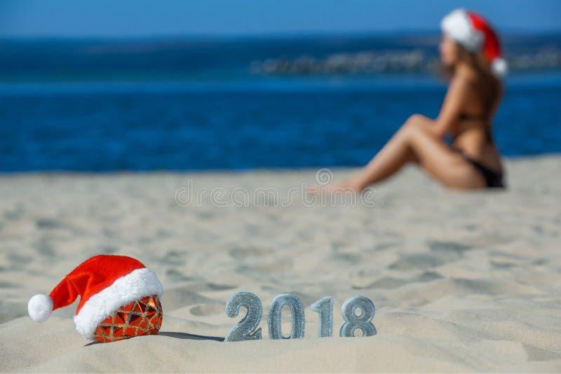 佩带在圣诞节球的红色圣诞老人帽子说谎在海滩,在新年的沙子旁边与银色衣服饰物之小金属片的 库存照片