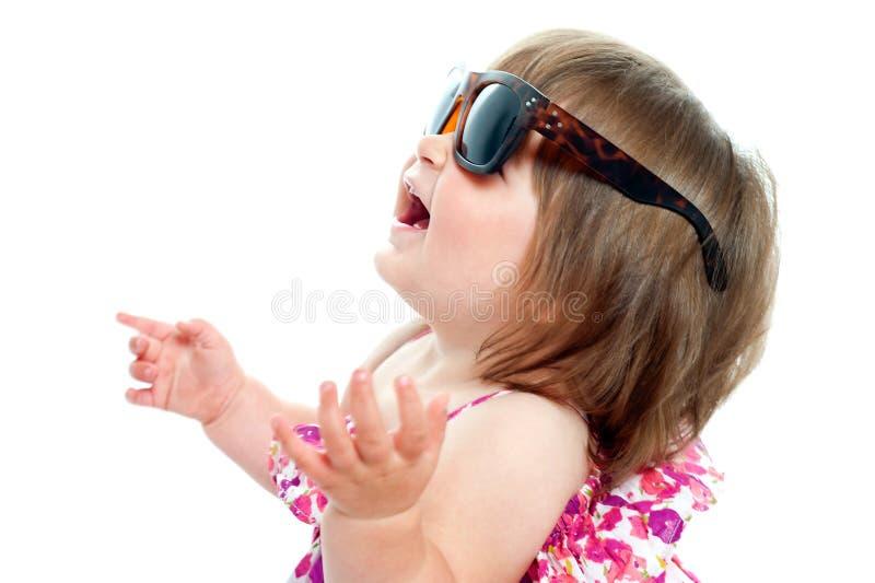 佩带在大小的太阳镜的女婴 免版税库存照片