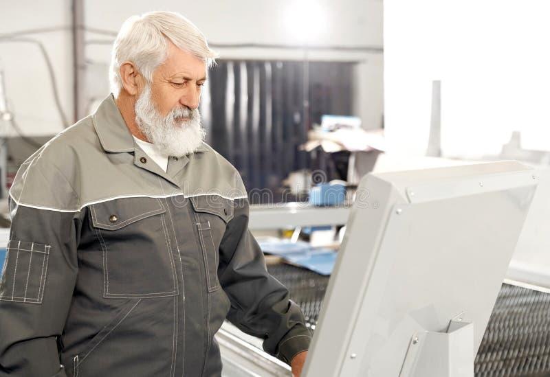 佩带在工厂的更老的人灰色一致的工作 库存照片