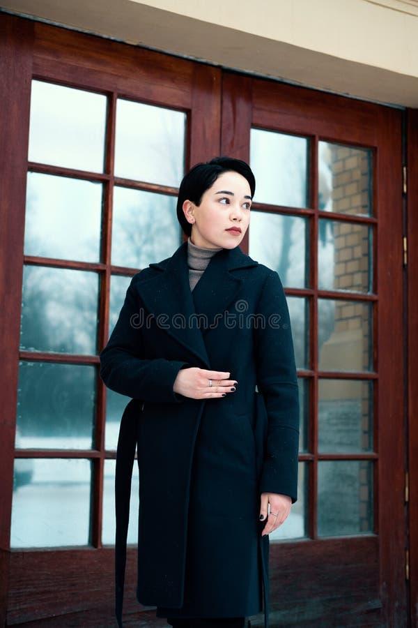 佩带在时髦蓝色外套身分的年轻时髦的亚裔妇女在城市街道的门框附近在凉快的冬日 库存图片