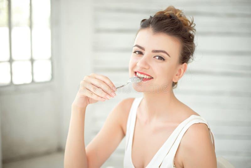 佩带在有匙子的白色汗衫的愉快的美丽的深色头发的妇女半身画象在嘴 库存照片