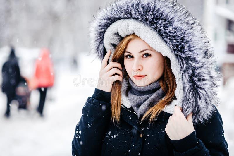 佩带在有敞篷的黑夹克的年轻美女室外画象 式样摆在街道 寒假概念 免版税库存图片