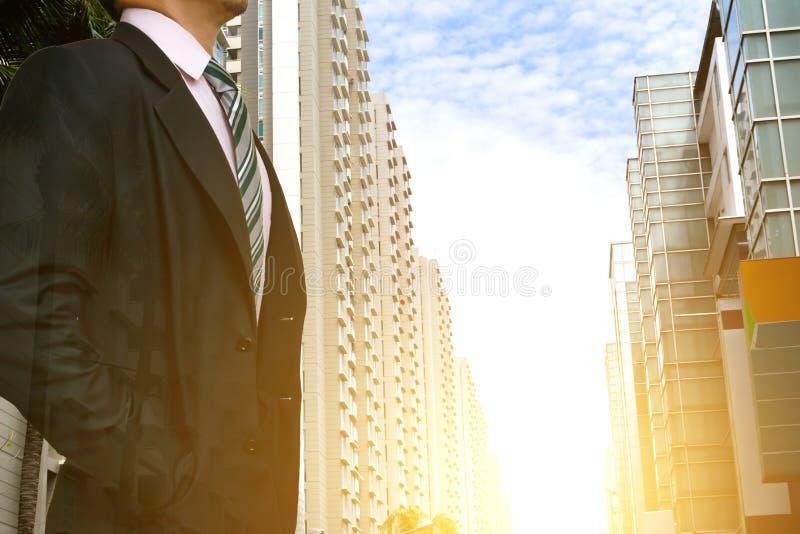 佩带在有看城市地平线的大厦的一个城市的商人领导日落现代生活的概念 库存图片