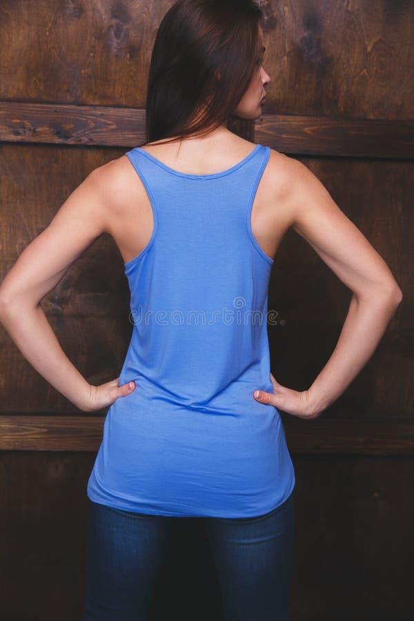 佩带在木墙壁前面的妇女蓝色上面 免版税库存图片