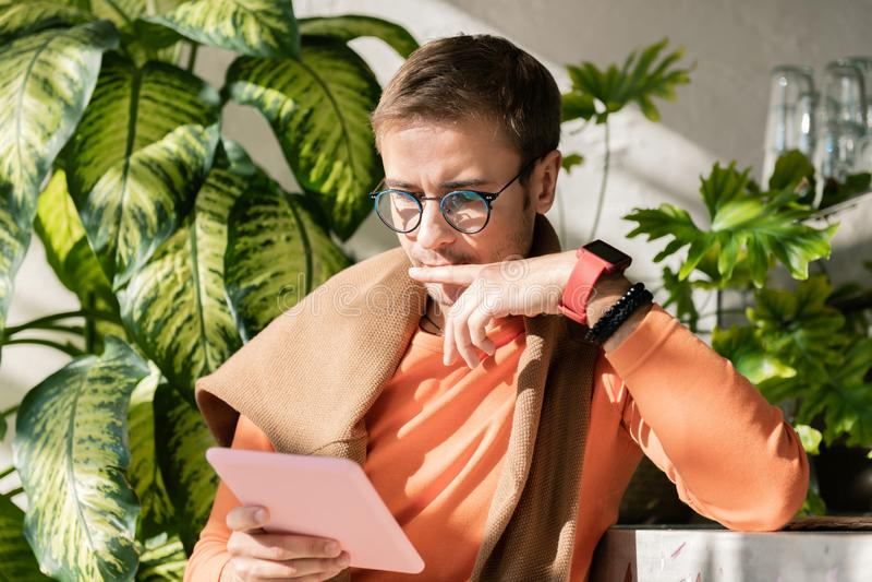 佩带在片剂的现代成功的企业家聪明的手表看书 库存照片