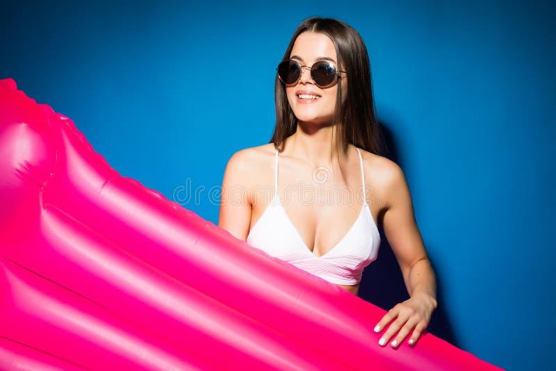 佩带在白色比基尼泳装的太阳镜的美丽的年轻女人举行与在蓝色背景隔绝的桃红色床垫 免版税库存照片