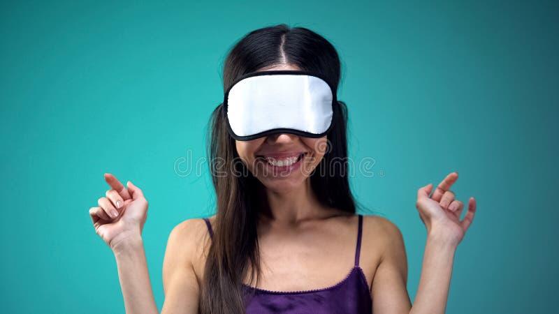 佩带在眼睛的睡衣的微笑的妇女眼罩,去睡,夜间 库存图片