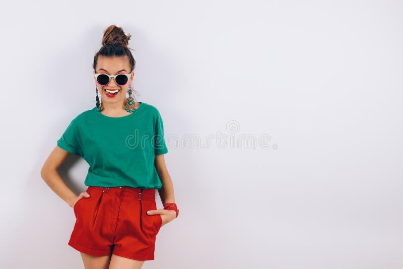 佩带在红色短裤和绿色T恤杉的太阳镜的美丽的行家妇女站立在白色墙壁和微笑附近 免版税库存图片