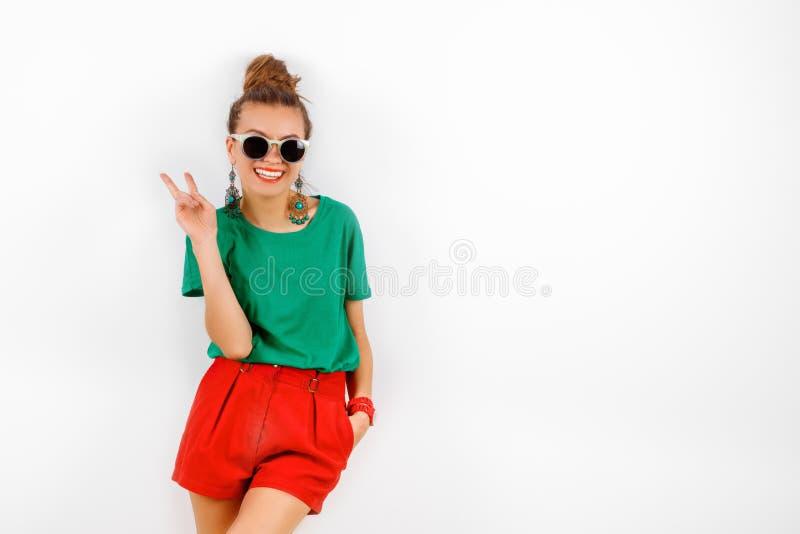 佩带在红色短裤和绿色T恤杉的太阳镜的美丽的妇女站立在白色墙壁,微笑和展示附近 图库摄影