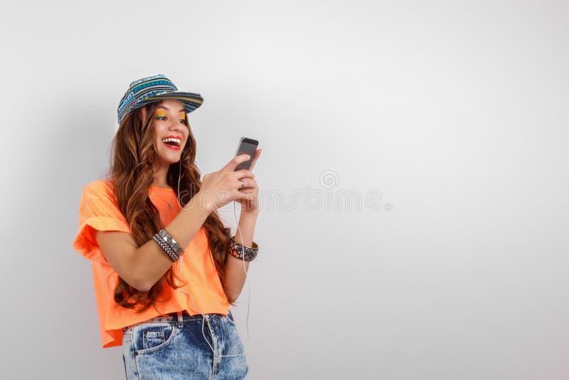 佩带在蓝色焰晕和橙色T恤杉听的音乐的年轻微笑的行家妇女在耳机在白色墙壁附近 图库摄影