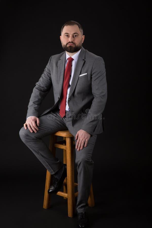 佩带在衣服,当安装在一张高脚椅子时和调查照相机的一个有胡子的时尚人的画象 o 库存图片