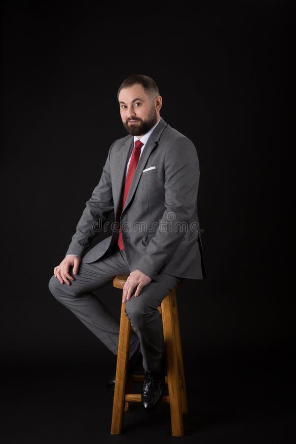 佩带在衣服,当安装在一张高脚椅子时和调查照相机的一个有胡子的时尚人的画象 o 免版税库存图片