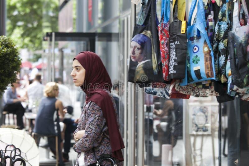 佩带在袋子的背景的女孩hijab与p的 免版税库存图片