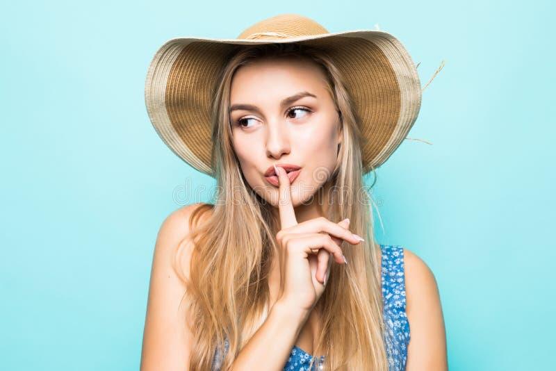 佩带大草帽陈列手指的欧洲迷人的妇女画象特写镜头在嘴唇保持秘密被隔绝在蓝色backgro 库存照片