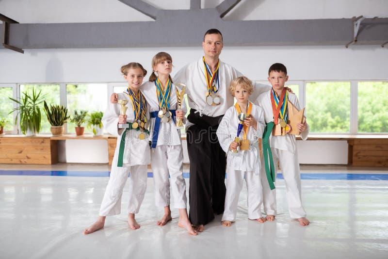 佩带奖牌和拿着他们的奖的男孩和女孩 库存照片