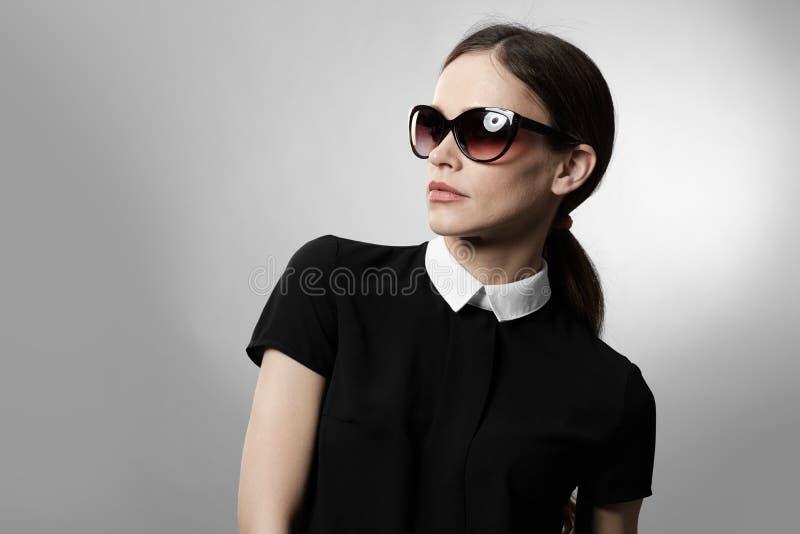 佩带妇女的俏丽的太阳镜 免版税库存图片
