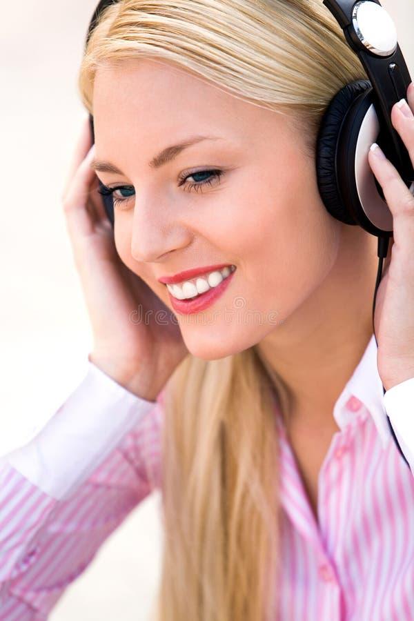 佩带妇女的耳机 免版税库存图片
