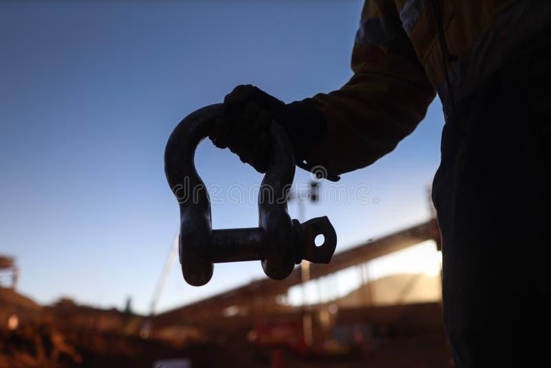 佩带安全手套藏品起重机的装配工人举有defocused起重机的17口气手铐在后面地面在日落期间 库存图片