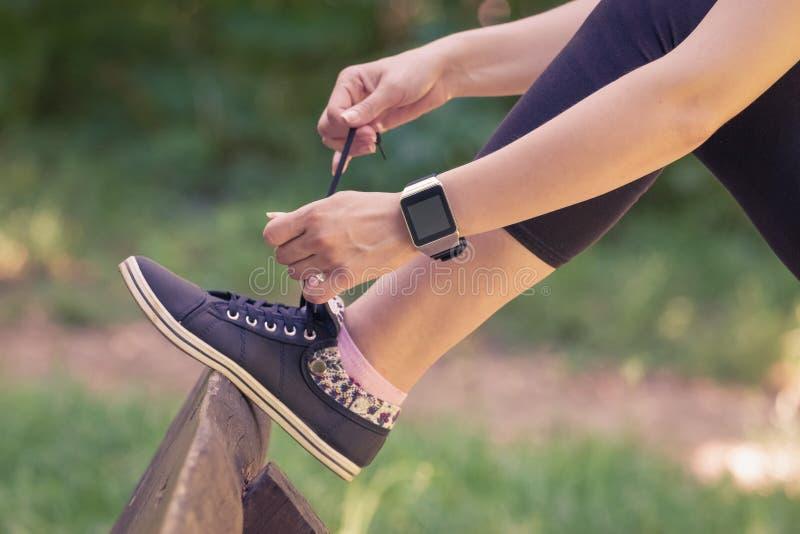 佩带巧妙的手表和栓鞋带的女性在公园 免版税库存图片