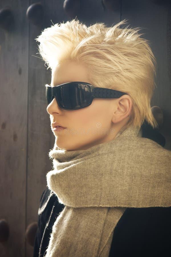 佩带年轻人的白肤金发的太阳镜 免版税图库摄影
