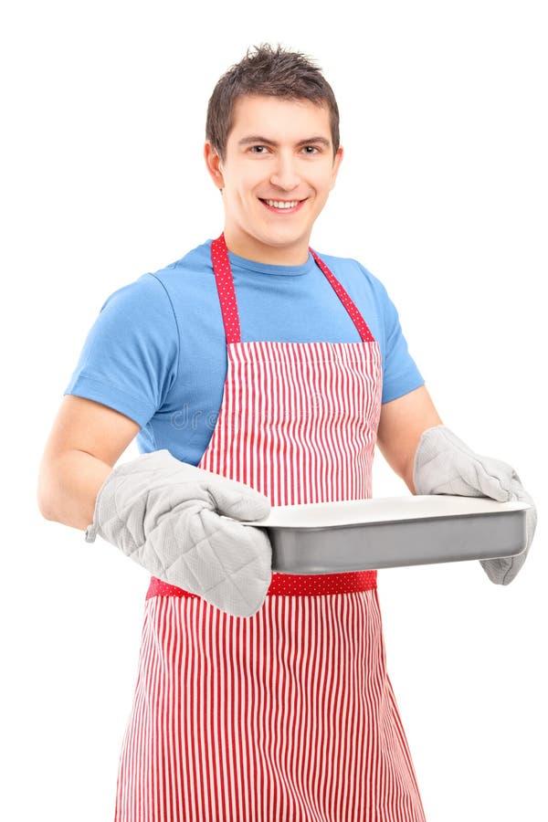 佩带微笑的人烹调手套和围裙 免版税库存照片