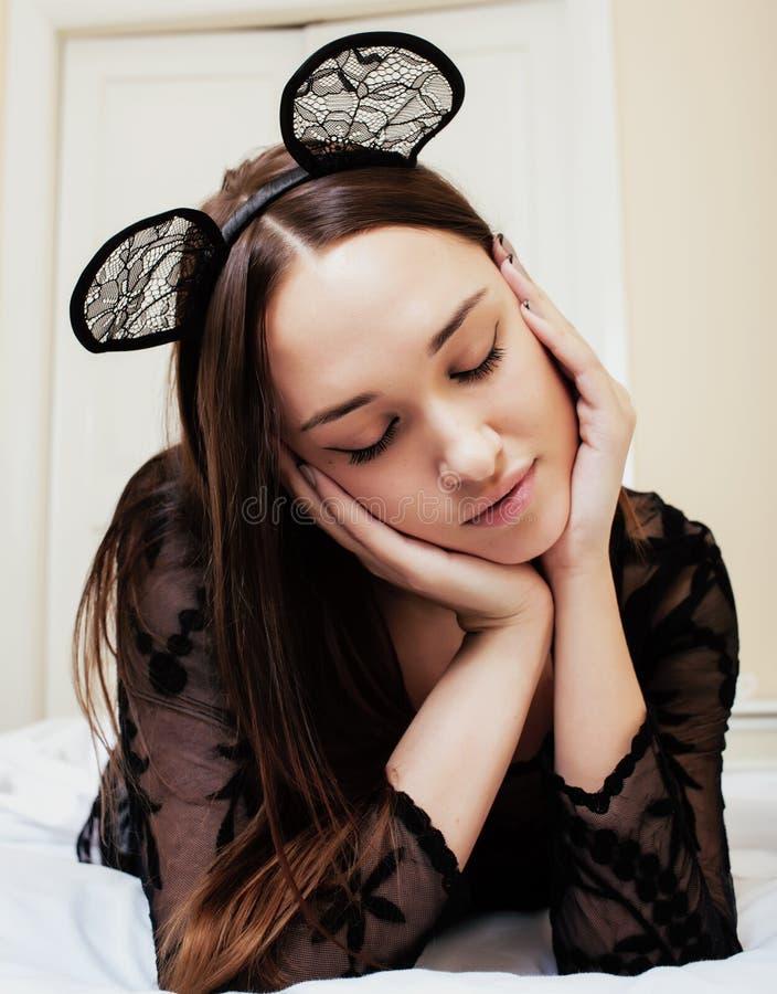 佩带性感的鞋带柳叶蒲公英属的年轻俏丽的深色的妇女,放置等待的作梦在床上 库存照片