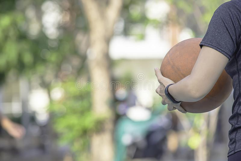 佩带手表和举行老篮球的妇女的手 免版税库存图片