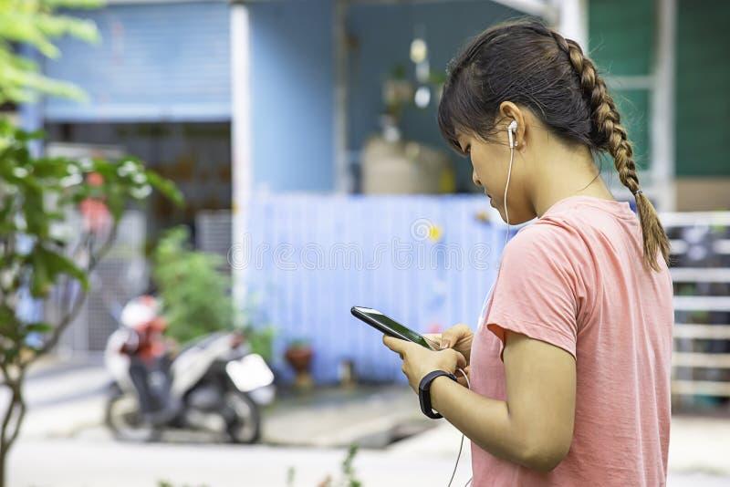 佩带手表和拿着的妇女的手耳机插头在耳机在轰隆亚伊公园背景树,暖武里 免版税库存图片
