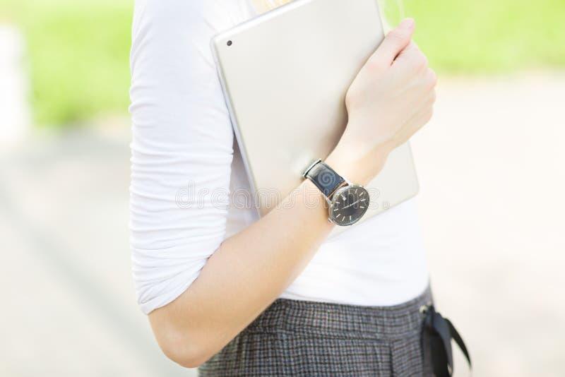 佩带手表和运载一种数字片剂的女性胳膊特写镜头户外 免版税库存图片