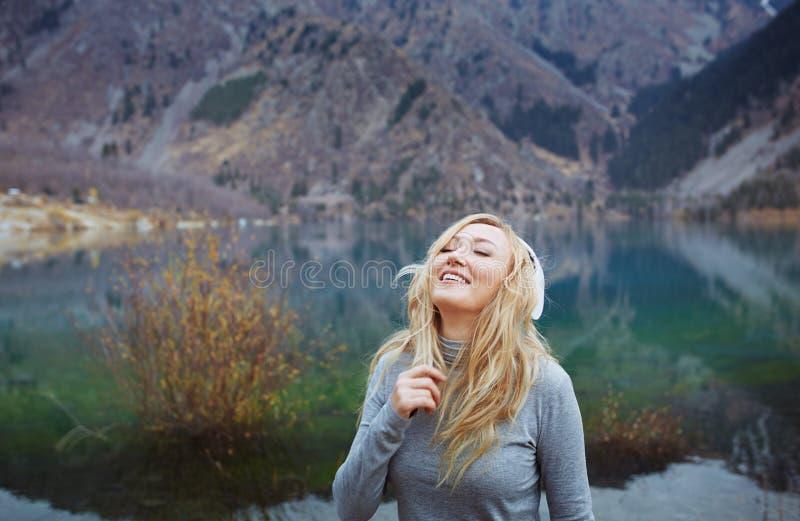 佩带无线耳机的妇女在湖 库存图片