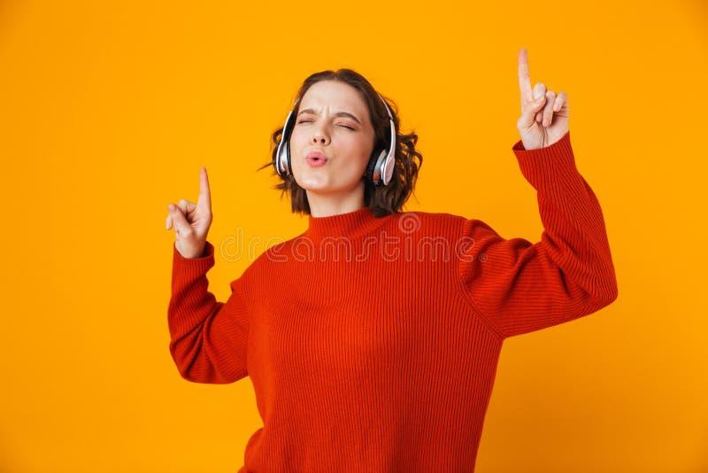 佩带无线耳机的欢悦妇女20s画象跳舞和唱歌 免版税库存图片