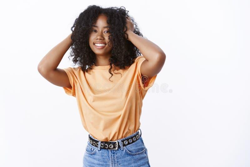 佩带时髦橙色T恤杉跳舞的可爱的无忧无虑的年轻女性非裔美国人愉快地微笑接触非洲 免版税库存图片