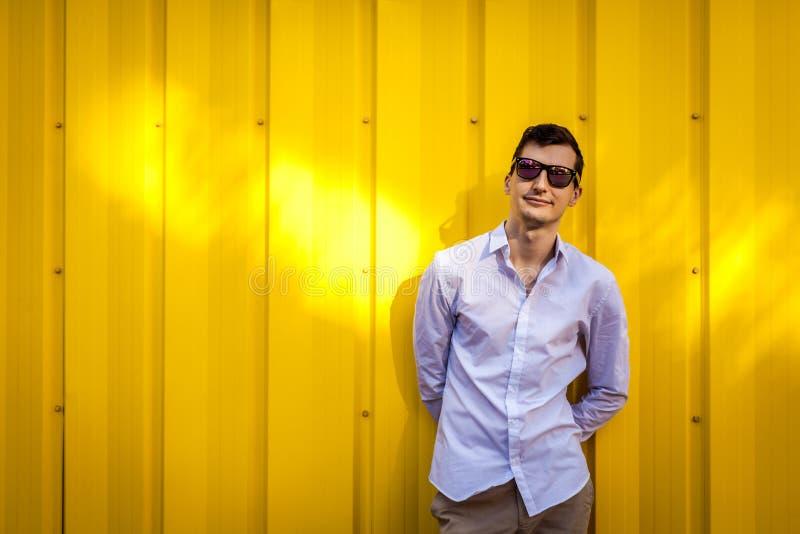 佩带时髦的夏天outfir的年轻英俊的人对黄色墙壁户外 行家人 库存图片