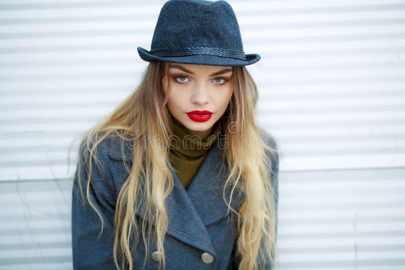 佩带时髦的辅助部件的年轻美丽的时髦的女人室外时尚画象  葡萄酒帽子,看照相机 免版税库存图片
