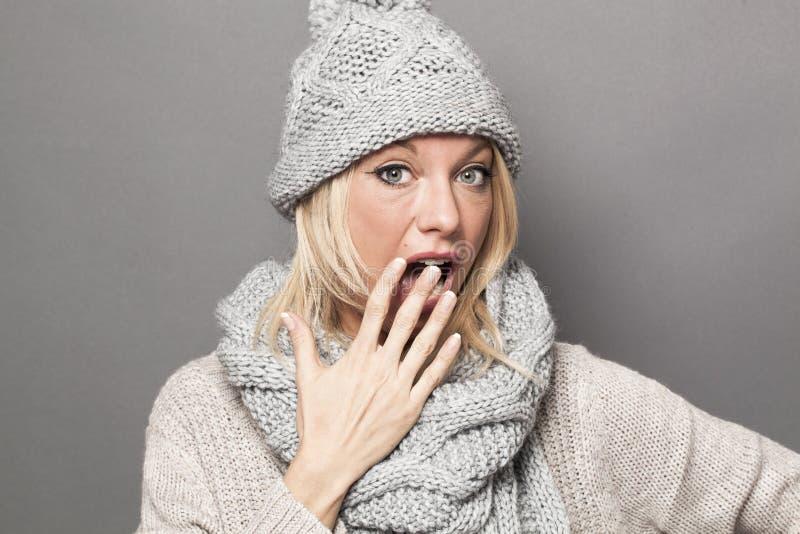 佩带时兴的冬天的震惊年轻白肤金发的女孩穿衣 库存照片