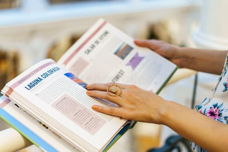 佩带最低纲领派当代首饰阅读书的妇女在图书馆商店 库存图片