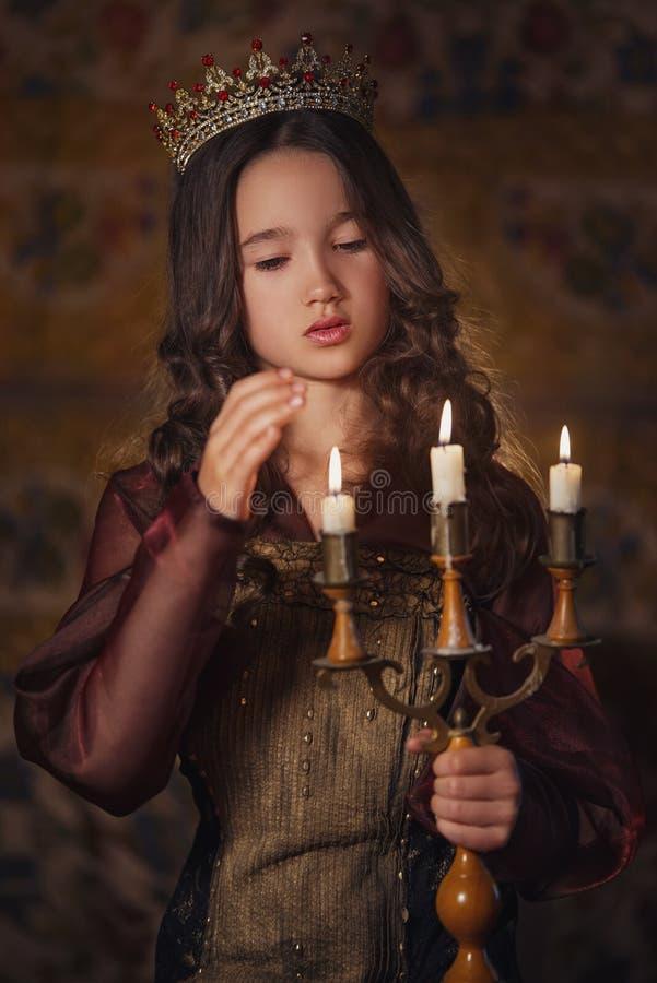 佩带有烛台的逗人喜爱的女孩画象一个冠在手上 年轻女王/王后或公主 免版税库存照片