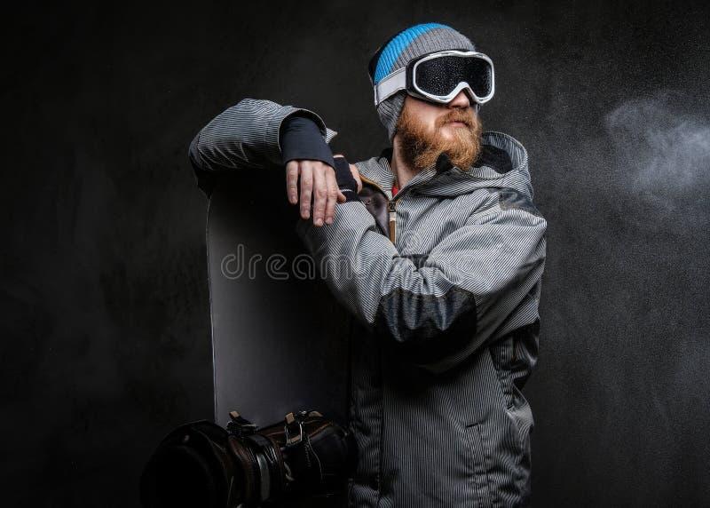 佩带极端雪板运动的红头发人有胡子的人一种充分的设备倾斜在雪板和看,被隔绝 免版税库存照片
