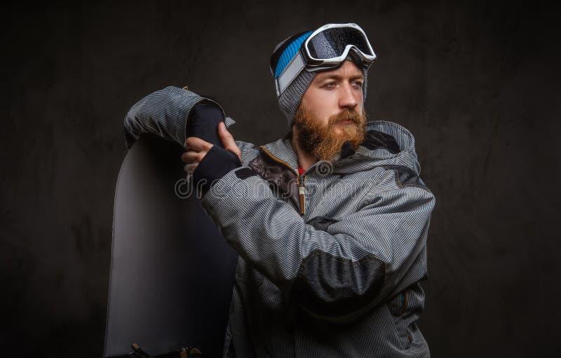 佩带极端雪板运动的红头发人有胡子的人一种充分的设备倾斜在雪板和看,被隔绝 库存图片