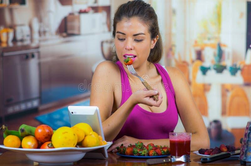 佩带桃红色上面的少妇享用健康早餐,吃草莓和微笑,家庭厨房背景 库存照片