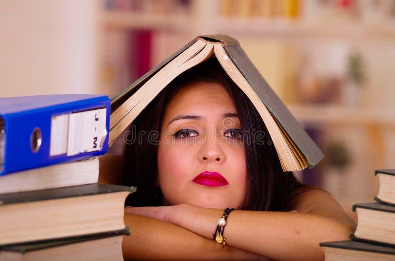 佩带桃红色上面说谎的年轻深色的妇女弯曲在有堆的书,在头安置的开放书书桌,疲乏的脸面护理 图库摄影