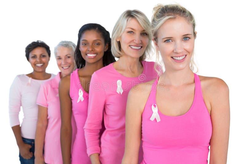 佩带桃红色和丝带乳腺癌的微笑的妇女 库存照片
