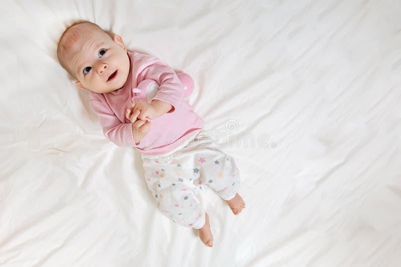 佩带桃红色身体的逗人喜爱的可爱的女婴顶视图和特写镜头画象在卧室 想象 婴儿放松的微笑, 库存图片