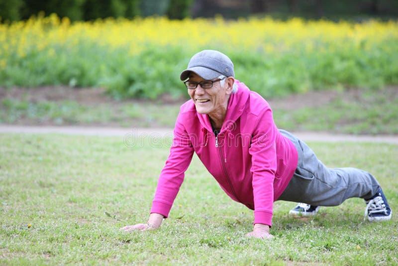 佩带桃红色附头巾皮外衣做的资深日本人在草坪增加 免版税图库摄影