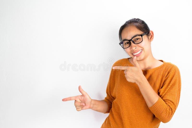 佩带橙色衬衣和镜片在白色背景的亚裔妇女微笑和看指向与两的照相机 免版税库存图片