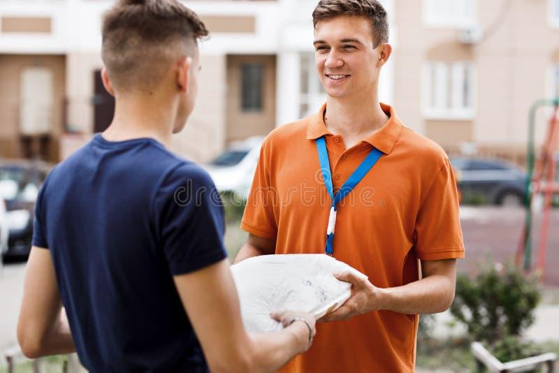 佩带橙色T恤杉和名牌的一个微笑的人交付一个小包到客户 友好的工作者,高 库存照片